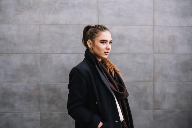 Elegante joven en abrigo con bufanda cerca de pared gris