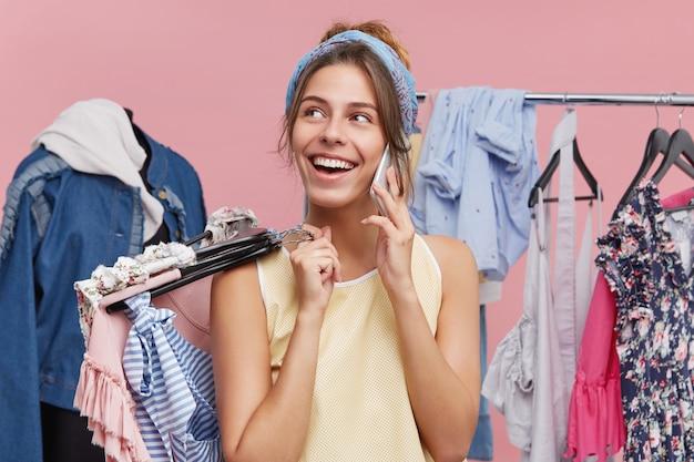 Elegante joven adicta a las compras hablando por teléfono móvil con su amiga, alardeando de sus compras mientras compra en el centro comercial de la ciudad, de pie en el estante lleno de coloridas prendas de moda