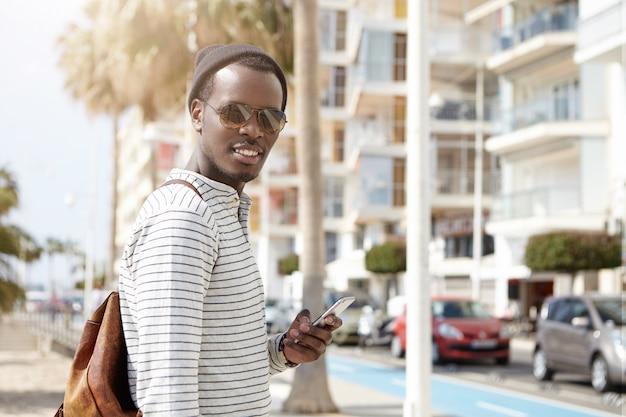 Elegante joven afroamericano en tonos y sombrero que busca ubicaciones a través de aplicaciones en línea para viajes o navegación gps, usando 3g y 4g en el teléfono móvil mientras camina en metrópolis extranjera