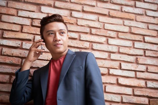 Elegante joven asiático de pie delante de la pared de ladrillo y sosteniendo el teléfono inteligente al oído