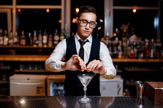 Elegante joven barman prepara un delicioso cóctel