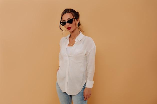 Elegante joven caucásica con cabello oscuro y labios rojos posando sobre pared aislada