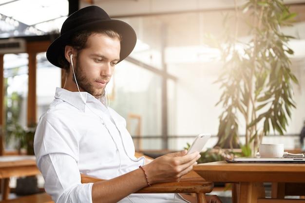 Elegante joven caucásico con sombrero negro enviando mensajes de texto sms o leyendo publicaciones a través de las redes sociales usando wifi gratuito en su teléfono móvil durante el desayuno en la acogedora cafetería y escuchando música en auriculares