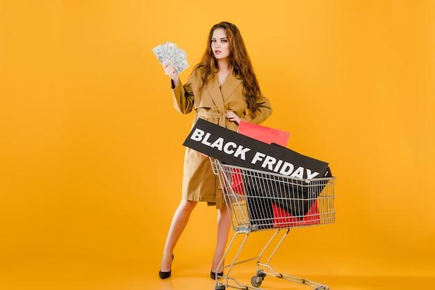 Elegante joven con dinero tiene signo de viernes negro en carretilla de mano con coloridas bolsas de compras y cinta de señal aislada sobre amarillo