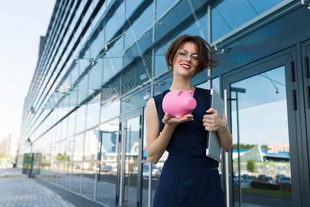 Elegante joven empresaria hermosa sostiene una alcancía en el fondo de un edificio de centro de negocios