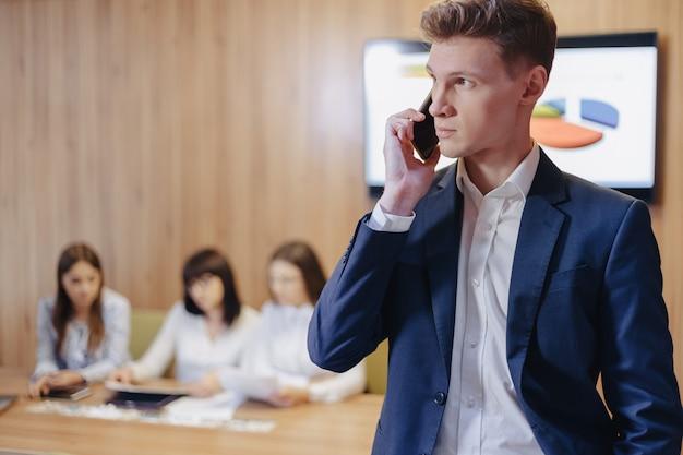 Elegante joven empresario vistiendo una chaqueta y camisa con gente hablando por un teléfono móvil