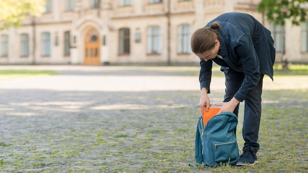 Elegante joven estudiante arreglando su mochila