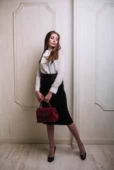Elegante joven en falda y blusa con bolso en la habitación.