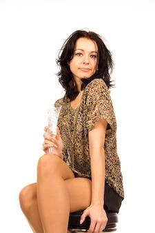 Elegante joven fiestera adolescente disfrutando de una copa de vino o champán de un vaso largo estriado mientras está sentado en un taburete, aislado en blanco