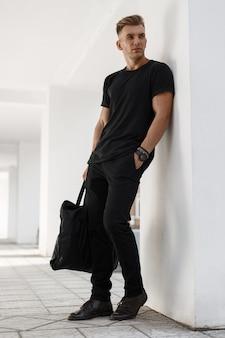 Elegante joven guapo con un peinado en una camiseta negra, pantalones y ramas con una bolsa negra se encuentra cerca de una pared blanca