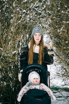 Elegante joven madre caminando con su hija en la carriola en el parque de invierno cubierto de nieve.