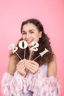 Elegante joven morena alegre con cabello rizado y hombros desnudos tiene un número de madera para el concepto de año nuevo sobre un fondo rosa