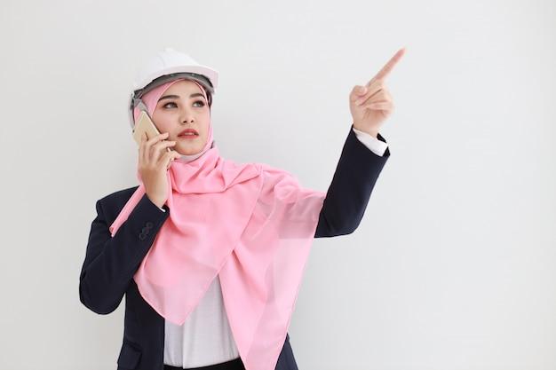 Elegante joven musulmana asiática vistiendo traje azul sonriendo confiado, señalando y usando el teléfono móvil