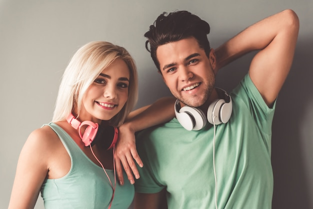 Elegante joven pareja con auriculares está mirando a cámara.