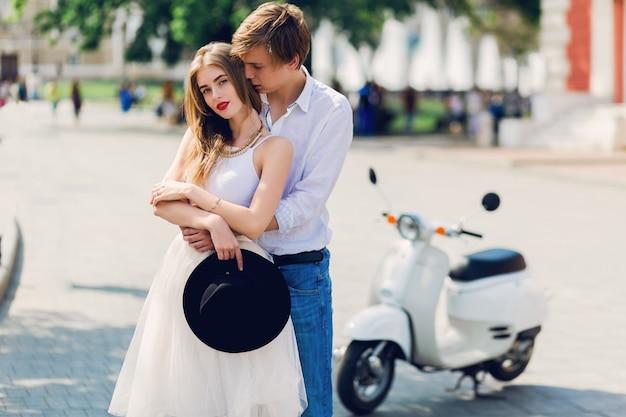 Elegante joven pareja de enamorados abrazándose, caminando en la vieja ciudad europea
