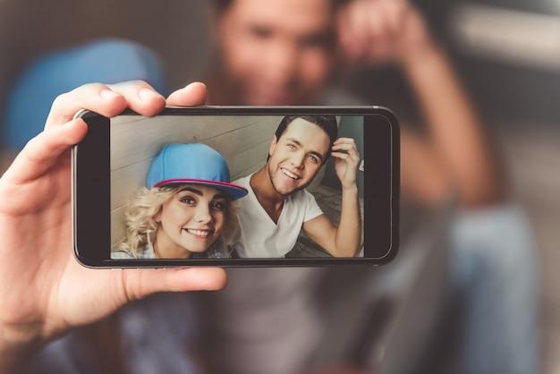 Elegante joven pareja en mayúsculas está haciendo selfie.