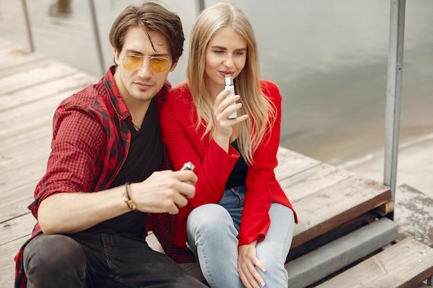 Elegante joven pareja con vape en una ciudad