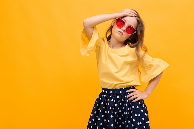 Elegante joven posando aislado sobre un fondo amarillo studio