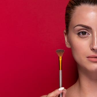 Elegante joven sosteniendo pincel de maquillaje