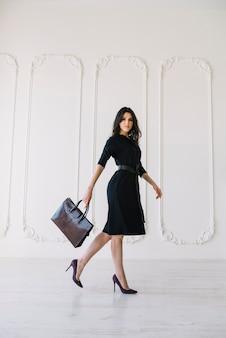 Elegante joven en vestido con bolso posando en la habitación