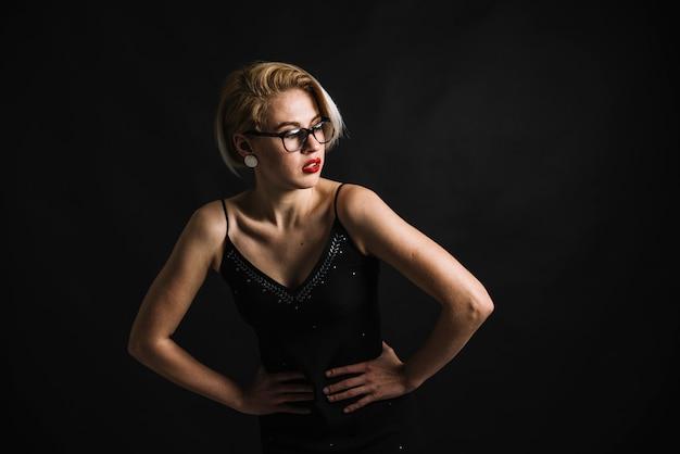 Elegante joven en vestido en la oscuridad