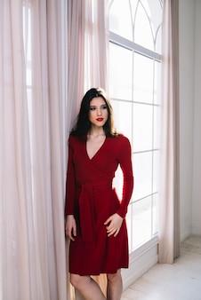 Elegante joven en vestido rojo junto a la ventana en la habitación