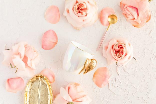 Elegante juego de té o café en colores pastel con flores de color rosa, plato de hojas doradas y cuchara con rosas y pétalos