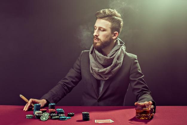 Elegante jugador de poker barbudo en la mesa con whisky y cigarros