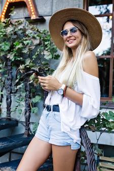 Elegante linda chica vestida con camisa blanca y pantalones cortos de mezclilla, sombrero y gafas de sol posa con teléfono inteligente junto a plantas verdes y luces