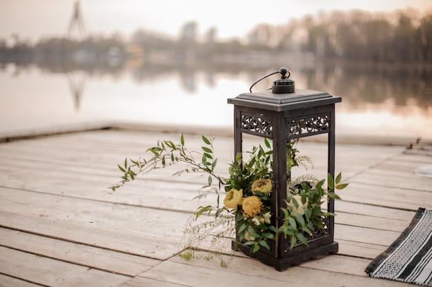 Elegante linterna de hierro decorada con flores tropicales como decoración de boda en la orilla del río