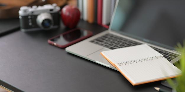Elegante lugar de trabajo con computadora portátil y suministros de oficina en mesa negra