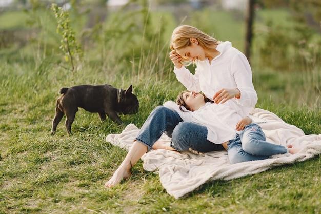 Elegante madre con hija en un bosque de verano