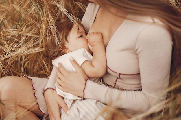 Elegante madre con linda hijita en un campo