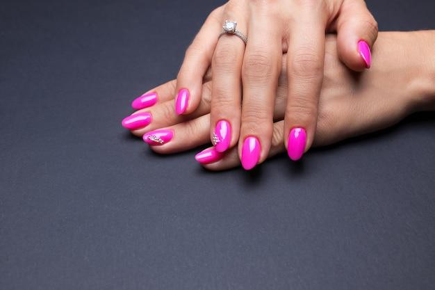 Elegante manicura rosa sobre un fondo negro