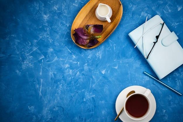 Elegante maqueta flatlay de negocios con taza de té negro, agenda con gafas y bolígrafo, soporte para leche en bandeja de madera sobre fondo de cemento azul con copyspace