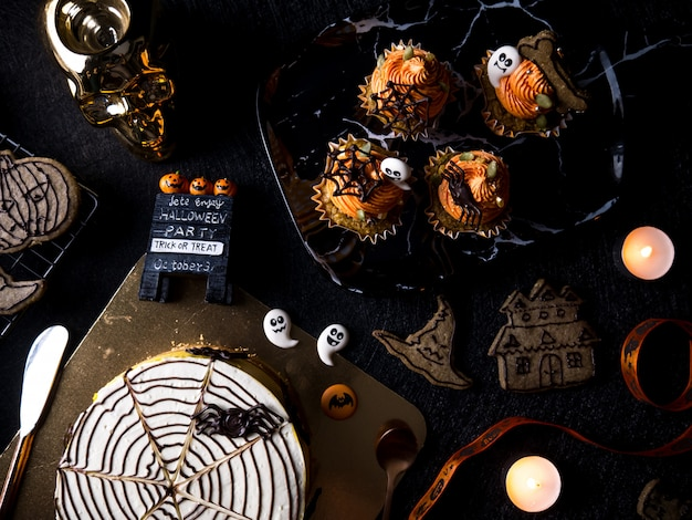 Elegante mesa de fiesta de comida de halloween con magdalena de calabaza y galletas.