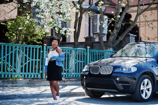Elegante modelo afroamericano con sombrero de anteojos, chaqueta de jeans y falda negra que se presenta al aire libre contra un automóvil deportivo negro.