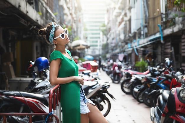 Elegante modelo con camisa verde y pañuelo posa en el estacionamiento con muchos scooters