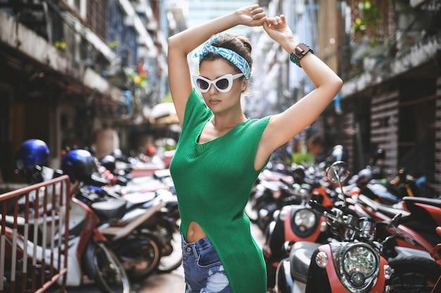 Elegante modelo con camisa verde y pañuelo posando en el estacionamiento con muchos scooters