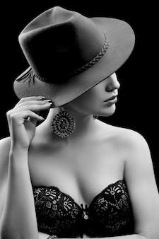 Elegante modelo femenino con un sombrero ocultando su rostro