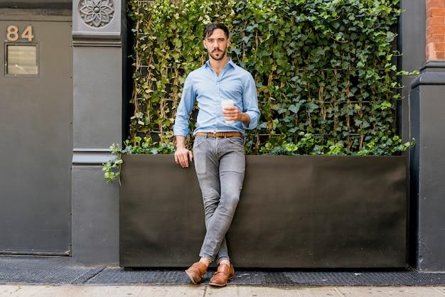 Elegante modelo masculino tomando café