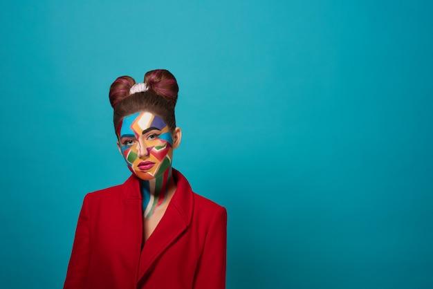 Elegante modelo posando con pop art maquillaje en la cara