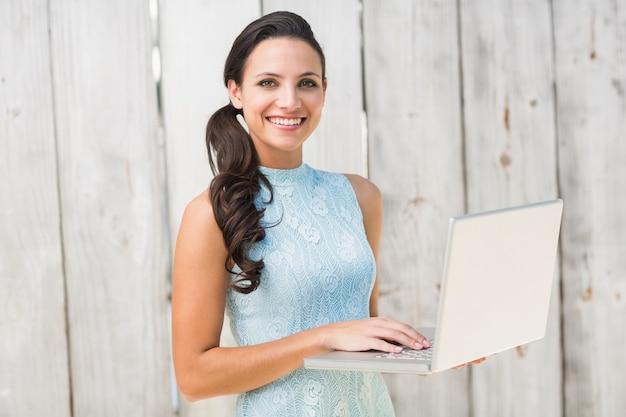 Elegante morena usando una laptop