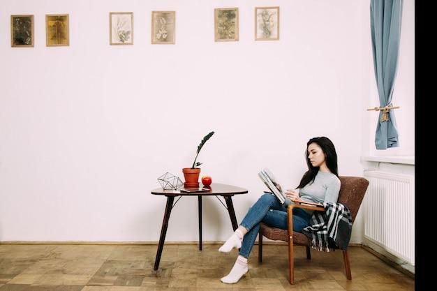 Elegante morena vestida de estilo casual lee revista sentada