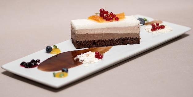 Elegante mousse triple de chocolate, decorado con frutas del bosque y salsa de chocolate.