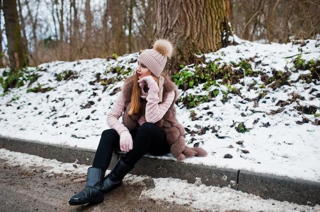 Elegante mujer en abrigo de piel y sombreros en día de invierno en sentado borde de carretera.