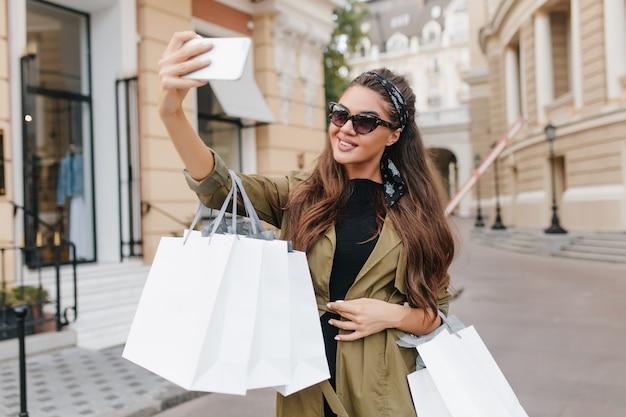 Elegante mujer adicta a las compras haciendo selfie con sonrisa feliz sosteniendo bolsas de papel