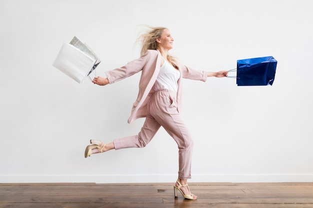 Elegante mujer adulta corriendo con bolsas de compras