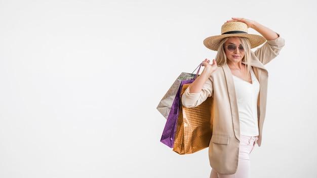 Elegante mujer adulta sosteniendo bolsas de compras con espacio de copia