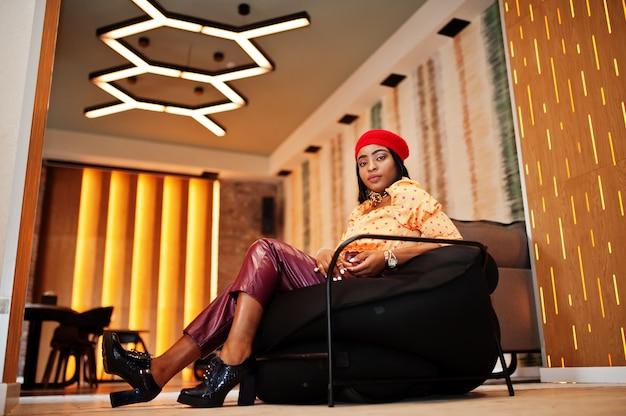 Elegante mujer afroamericana en boina francesa roja, blusa de lunares con cadena de cuello dorado grande y pantalones de cuero sentarse en puf